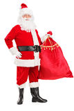 Santa Claus holding a bag full of gifts. Full length portrait of a Santa Claus holding a bag full of gifts on white background Stock Images