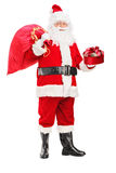 Santa Claus holding a bag and gift. Full length portrait of a Santa Claus holding a bag full of presents and gift  on white background Stock Photography