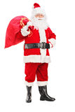 Santa Claus holding a bag on his back. Full length portrait of a Santa Claus holding a bag full of gifts on his back on white background Royalty Free Stock Photo