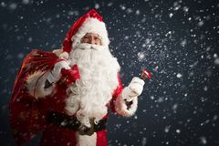 Santa Claus holding a bag with presents and ringing a bell on a dark background. With snow stock image