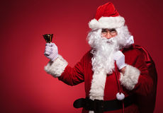 Santa claus holding bag on shoulder and a bell in his right hand Royalty Free Stock Photography
