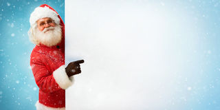Santa Claus holding banner with blue space for Your Text. / Merry Christmas & New Year's Eve concept / Closeup on blurred blue background Royalty Free Stock Photos
