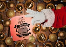 Santa claus holding bauble with christmas greeting in background Stock Images
