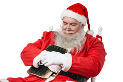 Santa claus holding bible while relaxing on chair Royalty Free Stock Image