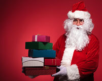 Santa claus holding a big pile of presents Stock Photography
