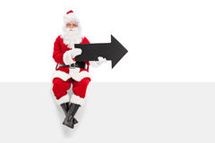 Santa Claus holding black arrow seated on a panel. Santa Claus holding black arrow seated on a blank panel isolated on white background stock photo