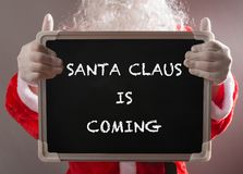 Santa Claus holding a black chalk board written SANTA CLAUS IS COMING Royalty Free Stock Image