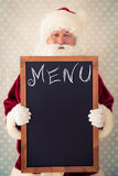 Santa Claus holding blackboard Royalty Free Stock Photography