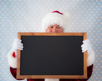 Santa Claus holding blackboard Royalty Free Stock Photo