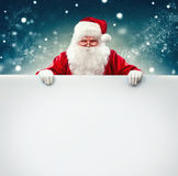 Santa Claus holding blank advertisement banner stock image