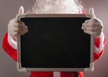 Santa Claus holding a blank chalk board good for texts to be added. Santa Claus holding blank chalk board good for texts to be added Royalty Free Stock Images