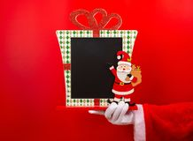 Santa Claus holding a blank Christmas decorated chalk board good for texts to be added on red. Background stock photos