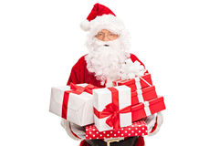 Santa Claus holding a bunch of presents Stock Images