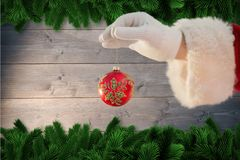 Santa claus holding christmas bauble Royalty Free Stock Images