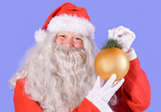 Santa Claus holding a Christmas decoration Stock Images