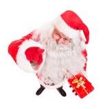 Santa Claus holding Christmas gift Stock Image