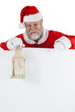 Santa claus holding christmas lantern on white board Royalty Free Stock Photography