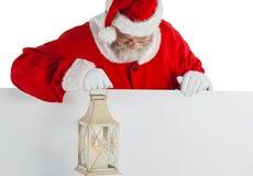 Santa claus holding christmas lantern on white board Stock Photos