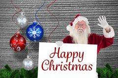 Santa claus holding christmas placard and waving. Against digitally generated background royalty free stock images