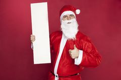 Santa Claus holding a copy space thumb up. On the red background Stock Photography