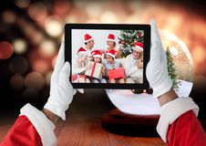 Santa claus holding a digital tablet with photo of christmas family Royalty Free Stock Photos