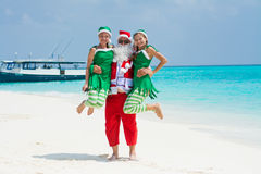 Santa Claus holding elvs on hands at the tropical beach Royalty Free Stock Photography
