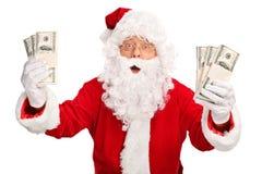Santa Claus holding few stacks of money Stock Images