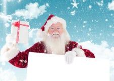 Santa claus holding a gift and blank placard. During snowfall royalty free stock photos