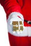 Santa claus holding a gift box in hand. Against white background Royalty Free Stock Image