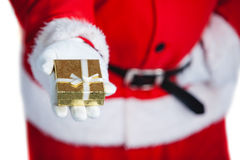Santa claus holding a gift box in hand. Against white background Stock Photos
