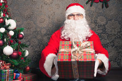 Santa Claus holding gift box or present at Christmas Stock Photography