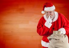 Santa claus holding gift sack with finger on lip Stock Images