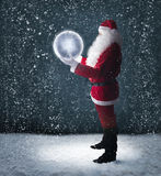Santa Claus holding glowing planet earth. Under falling snow royalty free stock photos