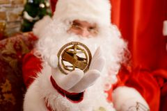Santa Claus holding gyroscope, sitting in arm chair royalty free stock photo