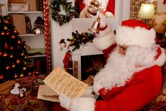 Santa Claus holding Hand bell and musical manuscript, music sheet stock image