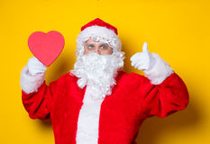 Santa Claus holding heart shape gift Stock Images