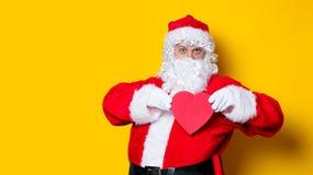 Santa Claus holding heart shape gift Royalty Free Stock Photo