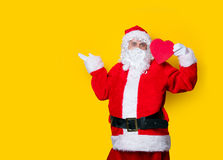 Santa Claus holding heart shape gift Royalty Free Stock Images