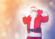 Santa Claus holding heart shape gift Stock Photography