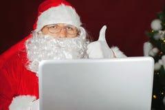 Santa Claus holding a laptop computer Stock Photo