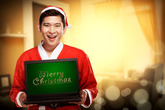 Santa Claus Holding Laptop With Merry Christmas Writing Royalty Free Stock Image