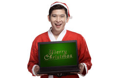 Santa Claus Holding Laptop With Merry Christmas Writing Stock Image