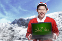 Santa Claus Holding Laptop With Merry Christmas Writing Stock Images