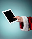 Santa Claus holding laptop. Ready for Christmas time on blue studio background Royalty Free Stock Photo