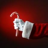 Santa Claus Holding Large Candy Cane över ett ljus till mörker - röda lodisar Royaltyfri Fotografi