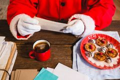 Santa Claus holding a letter. At home royalty free stock photography