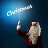 Santa Claus holding a light christmas word Stock Photos
