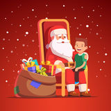 Santa Claus holding little smiling boy on his lap Royalty Free Stock Photography