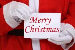 Santa Claus holding Merry Christmas card Stock Image