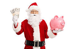 Santa claus holding money bundles and a piggybank. Claus holding money bundles and a piggybank isolated on white background Stock Images